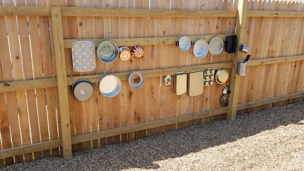 Outside fence of pots and pans attached for a preschool music wall at Children First Preschool Denton TX.